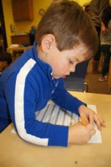 boy writing at preschool