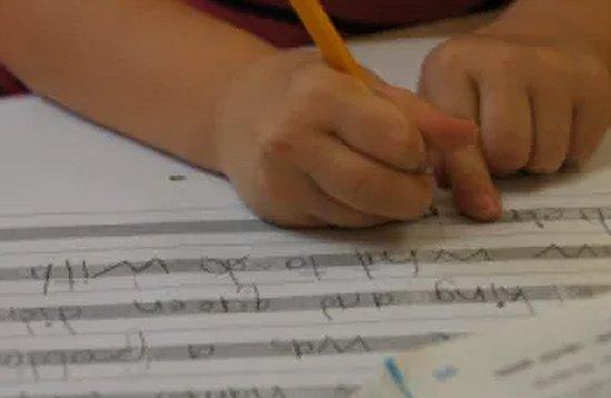 kindergarten child writing at preschool
