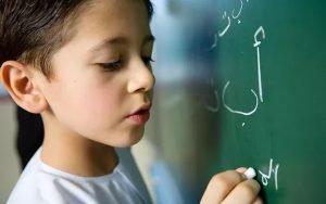 preschooler writing on chalkboard