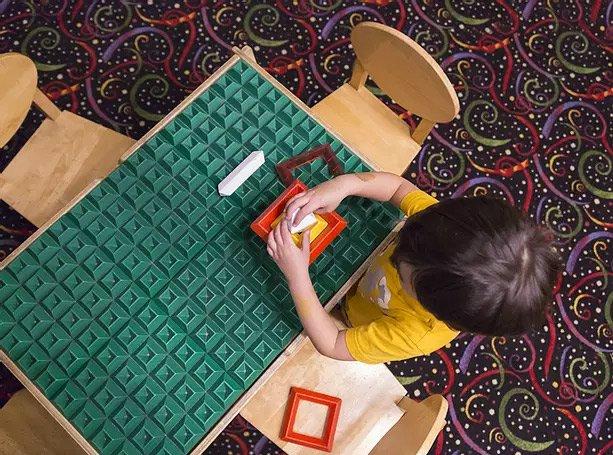 toddler playing at table at preschool
