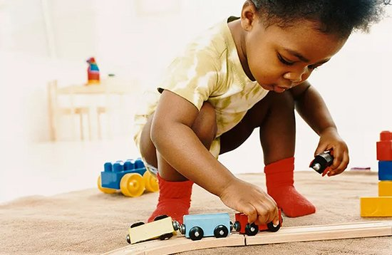 toddler playing with trains at preschool
